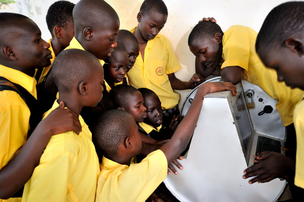 Young Ugandans gather around to use UNICEF's unique innovation the solar-powered Digital Drum, at Bosco Youth Centre in Gulu, Uganda.  The Digital Drum was this month chosen as one of Time Magazine's Best Inventions of 2011.   About 10 per cent of Ugandans currently use the Internet, and a majority of Ugandans live in rural settings with little to no access to information across areas of health, education, job training, and protection from violence and abuse. The poorest, most isolated and vulnerable children and youth are hit hardest from this lack of access when they do not benefit from crucial services and resources that could improve their health, safety and future. In response, UNICEF is developing these rugged computer kiosks that will serve as information access points aimed at youth and their communities.   The computers will be pre-loaded with dynamic multimedia content on health, job training, education opportunities, and other services.  The innovation is being developed and tested in Uganda by UNICEF's Technology for Development unit. The Digital Drum is a computer built into an oil drum. It was designed by UNICEF Uganda's Technology 4 Development Unit in partnership with other companies. The drums have been installed in youth centers and other areas so that kids can have access to computers. The computers have preloaded content that youth can access. (Bosco Youth Center, Gulu)