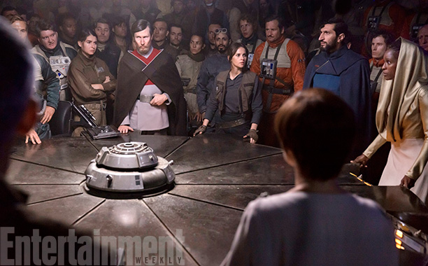 Rogue One: A Star Wars Story (2016) Felicity Jones (C) and Riz Ahmed (behind) - briefing room, with Felicity and the  Senator Jebel (guy in red and grey),  Senator Vaspar (guy in blue), Senator Pamlo (lady in gold). Also back of Mon Mothma's head